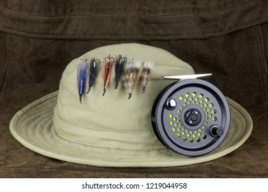 Salmon fishing flies on hat with fly fishing reel on an outdoor coat