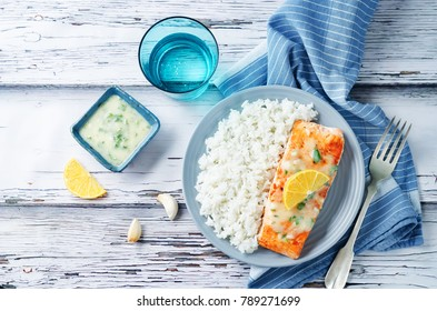 Salmon with Garlic Lemon Butter Sauce and rice on a wood background. toning. selective focus