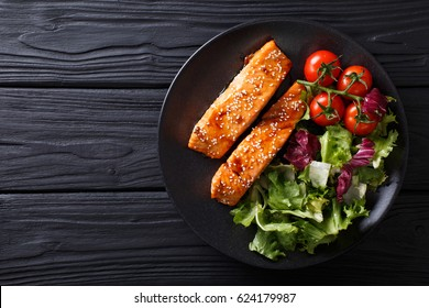 salmon in honey-soy glaze and fresh vegetable close-up on a plate. horizontal view from above