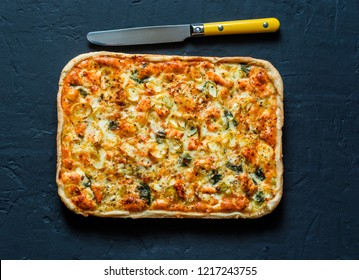 Salmon, leek, spinach, cheese puff pastry pie on dark background, top view