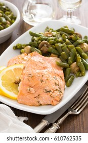 salmon with lemon and green beans on white dish