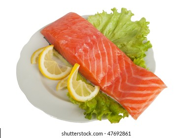 Salmon with lemon on salad leaves over white background