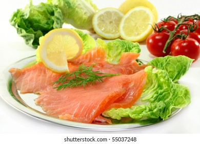 Salmon with lemon slices and dill on green salad