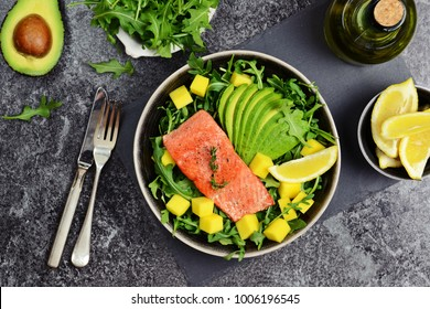 Salmon and mango salad on the dark background. Top view food