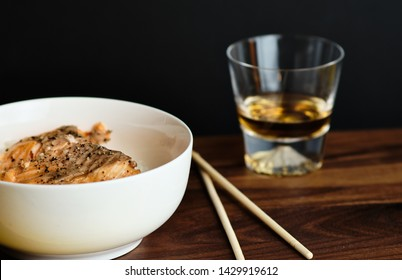 Salmon on top of a bed of rice in a white bowl next to chopsticks and a glass of whiskey