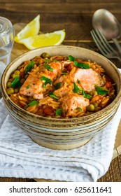 Salmon and orzo stew garnished with parsley and lemon