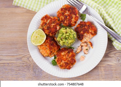 Salmon patties or cakes, lime and avocado on white plate. Fritters of fish. Salmon burgers. Healthy snack or take-away lunch bites, overhead