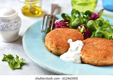 Salmon patties with mix salad leaves and yogurt sauce on a plate on light slate,stone or concrete background.Top view.