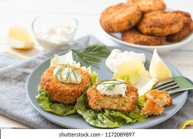 Salmon patties served on green salad with fresh dill, lemon slices and white sauce on top.