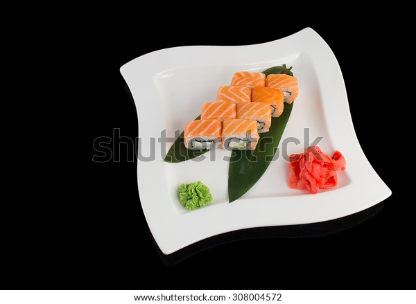 Salmon (philadelphia) sushi roll on a white plate over black background