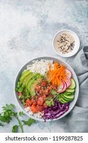 salmon poke bowl (avocado, salmon, carrot, cucumber, red cabbage, radish and rice), top view