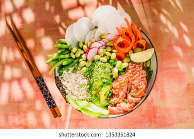 Salmon poke bowl with avocado, edamame beans, vegetables and rice. Sushi bowl. Living coral color trendy background sun light top view.Trendy healthy food.
