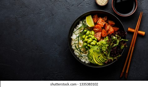 Salmon Poke bowl Raw fish salad Asian trendy food with soy beans edamame, rice, avocado and lettuce in bowl on dark background copy space