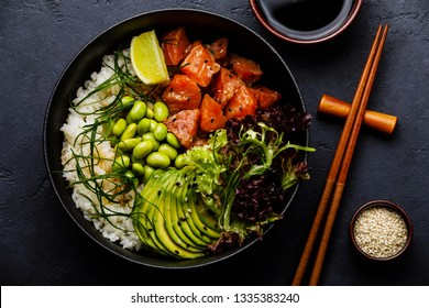 Salmon Poke bowl Raw fish salad Asian trendy food with soy beans edamame, rice, avocado and lettuce in bowl on dark background close-up