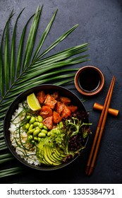Salmon Poke bowl Raw fish salad Asian trendy food with soy beans edamame, rice, avocado and lettuce in bowl on tropical leaf and dark background