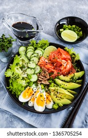 Salmon poke bowl served with avocado, eggs, cucumber and greens. Top view with copy space.