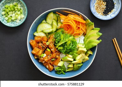 Salmon poke with pickled cucumber, carrots, avocado and seaweed