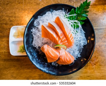 Salmon raw sashimi in  black plate on wooden table
