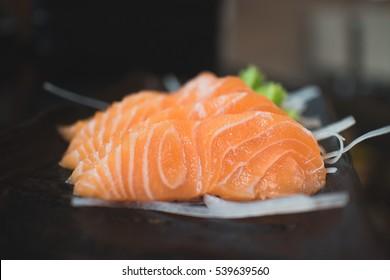 Salmon raw sashimi on black Japanese traditional dish on black table. Closed up.