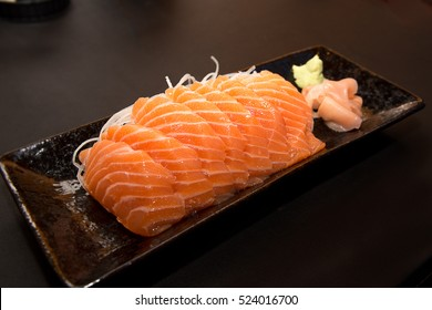 Salmon raw sashimi on brown Japanese traditional dish on black table. Closed up.