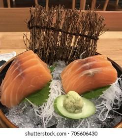 Salmon raw sashimi on brown Japanese traditional dish on black table.