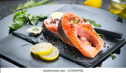 Salmon. Raw Trout Red Fish Steak served with Herbs and Lemon and olive oil on slate. Cooking Salmon, sea food. Healthy eating concept
