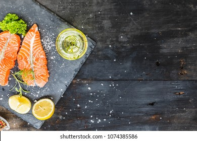 Salmon, Red fish medallions on slate tray with lemon and spices on old black smoked rustic wooden background, top view, copy space