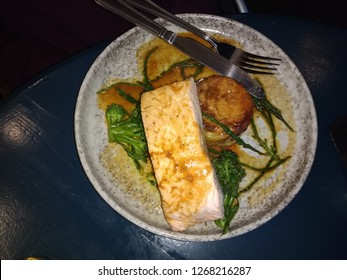 Salmon restaurant  meal with samphire and fresh healthy vegetables and sauce on grey plate  cutlery of knife, fork placed together on side viewed from above looking down