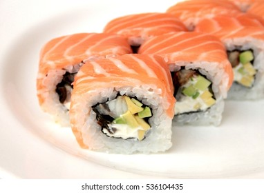 Salmon rice avocado caviar philadelphia sushi roll on a plate