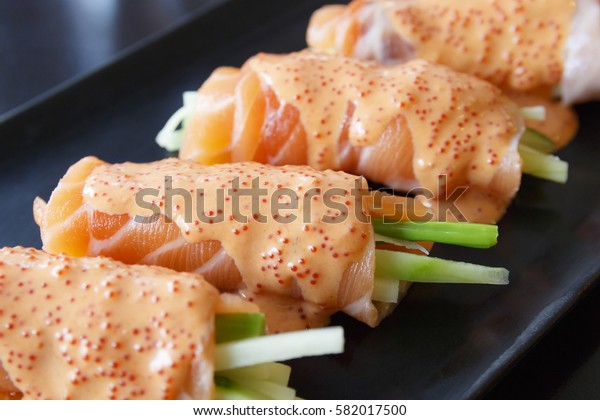 salmon roll and mentaiko sauce on black dish