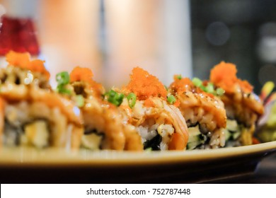 Salmon roll with spicy sauce on top with shrimp eggs. Selective focus.