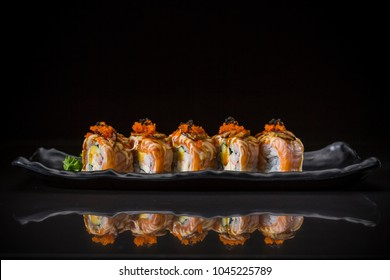 Salmon Roll topped Foie Gras Roll and sweet sauce,  traditional Japanese food on ceramic dish, Japanese food style, Sushi Menu, salmon sushi roll on black background, selective focus
