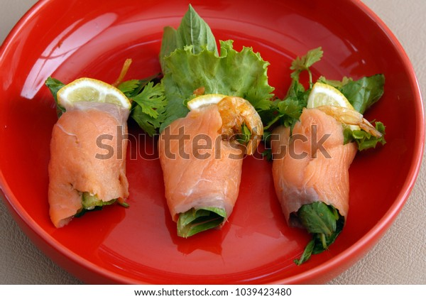 Salmon roll with various vegetable on red dish top view.