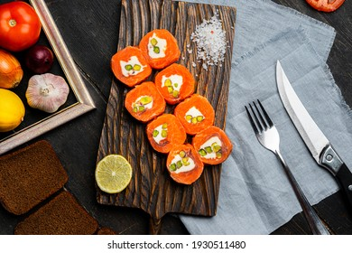 Salmon rolls with cream cheese and pistachios on a wooden cutting board. Luxury catering. Top view.