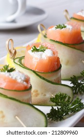 salmon rolls with cucumber, cream cheese and herbs closeup on a white plate vertical