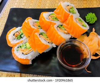 Salmon rolls are on the table with soysauce and horseradish