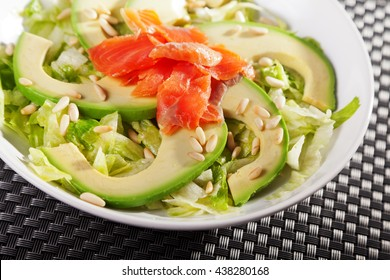 Salmon salad with avocado served in a salad bowl, one portion