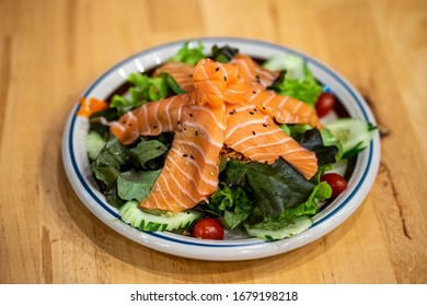 Salmon Salad with cherry tomatoes, cucumbers, baby spinach, fresh mint and basil. Home made food. Concept Healthy meal. Wooden table background. Top view. Close up.