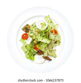 Salmon salad isolated on white background. Salmon, eggs, lettuce, tomatoes and pesto on white plate, top view