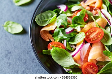 Salmon Salad with spinach, cherry tomatoes, corn salad, baby spinach, fresh mint and basil. Home made food. Concept for a tasty and healthy meal. Dark stone background. Top view. Close up.
