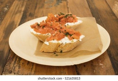 Salmon sandwiches, served as tapas in a bar, shot on a wooden table with copyspace