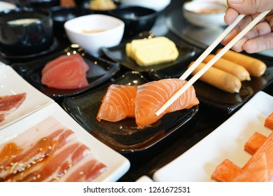 Salmon Sashimi - Hand holding chopsticks to pick fresh salmon sliced, Japanese food style.