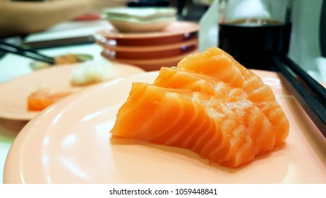 salmon sashimi in japanese conveyor belt restaurant, japan