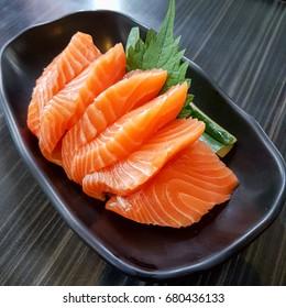 Salmon sashimi on black dish