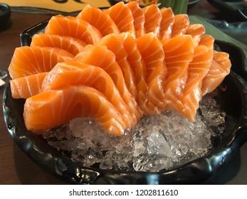 Salmon sashimi on ice in black dishes