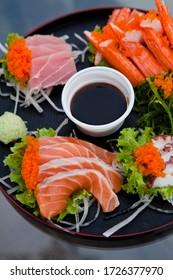 Salmon sashimi with tuna and sauce  in black plate.