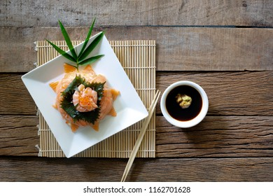 Salmon Sashimi in white dish on Sushi roll mat and Shoyu sauce with wasabi in white bowl all put on old brown wooden table / Select focus and space for texts