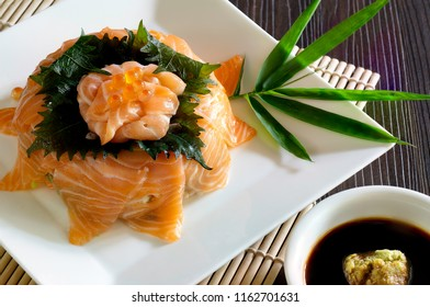 Salmon Sashimi in white dish on Sushi roll mat and Shoyu sauce with wasabi in white bowl all put on brown wooden table / Select focus