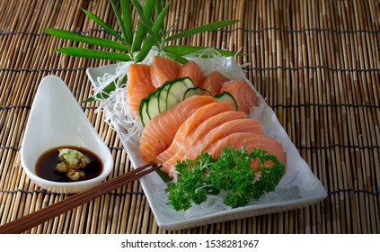 Salmon sashimi in white dish with shoyu sauce with wasabi in white bowl and chopsticks all put on bamboo mat, Japanese food, Still life and select focus