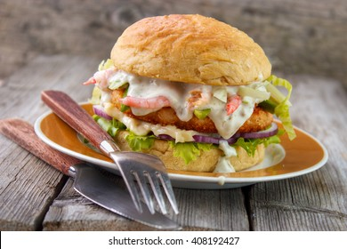 Salmon and shrimp burger , mayonnaise on bottom bun , breaded salmon shrimp patty and tartar sauce with fresh shrimps on gray wooden boards background